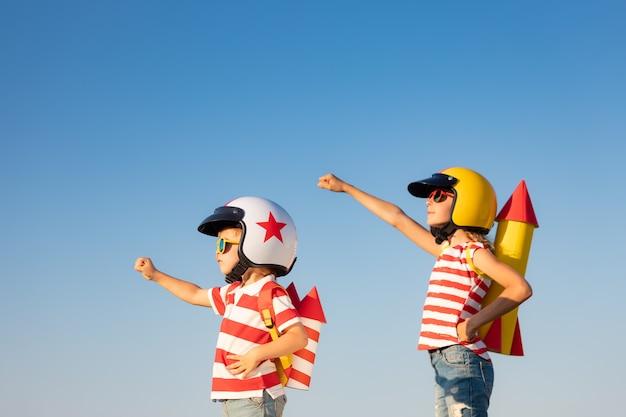 Crianças felizes brincando com um foguete de brinquedo contra o fundo do céu de verão