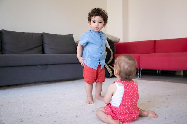 Crianças felizes brincando juntos em casa. menino cacheado de corrida mista em pé. vista traseira da menina sentada no tapete com os pés descalços na sala de estar. conceito de férias, fim de semana e infância