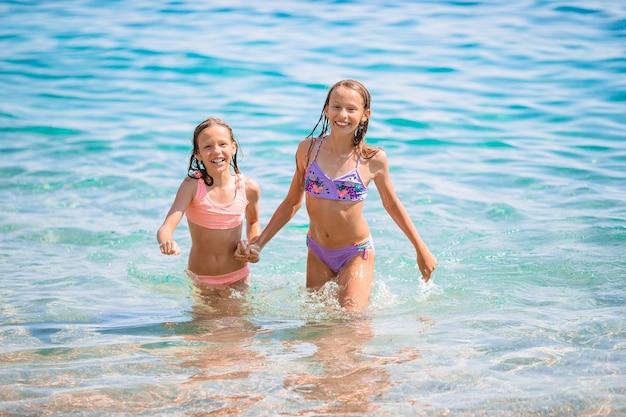 Crianças felizes brincando nas ondas durante as férias de verão em uma praia tropical