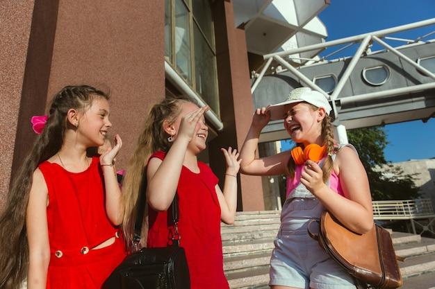 Crianças felizes brincando nas ruas da cidade em um dia ensolarado de verão em frente a um edifício moderno. grupo de crianças felizes ou adolescentes se divertindo juntos. conceito de amizade, infância, verão, férias.