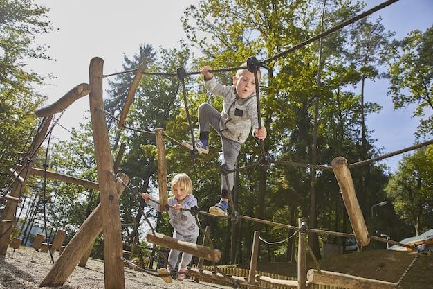 Crianças felizes brincando no parquinho de madeira durante o dia