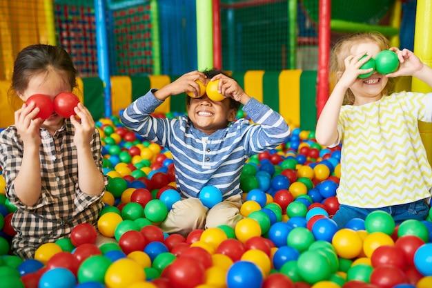 Crianças felizes brincando no poço da bola