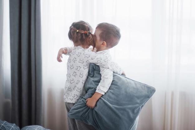 Crianças felizes brincando no quarto branco. menino e menina, irmão e irmã brincam na cama de pijama. roupa de dormir e roupa de cama para bebés e crianças. família em casa.