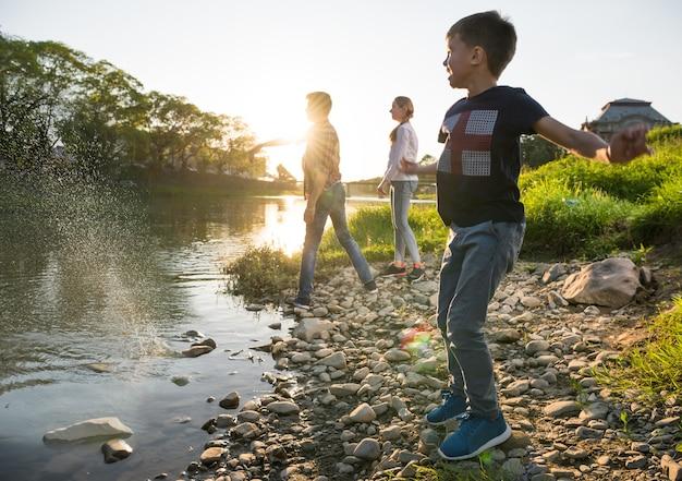Crianças felizes brincando perto do rio. meninos e uma menina jogando seixos no rio. dia ensolarado de verão
