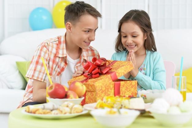 Crianças felizes com bolo e presente na festa de aniversário