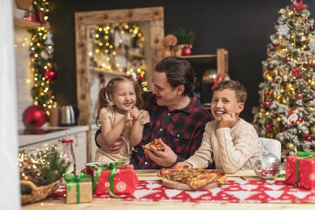 Crianças felizes com o pai comendo pizza na cozinha decorada para o natal