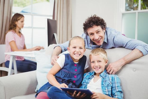 Crianças felizes com o pai pelo sofá em casa