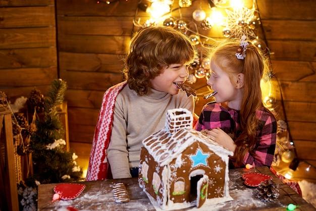 Crianças felizes com pão de gengibre de natal em um quarto decorado para o feriado.