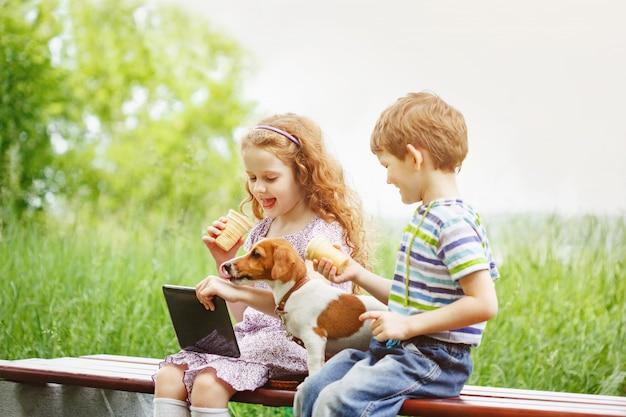 Crianças felizes com um cachorro amigo filhote brincando no tablet pc
