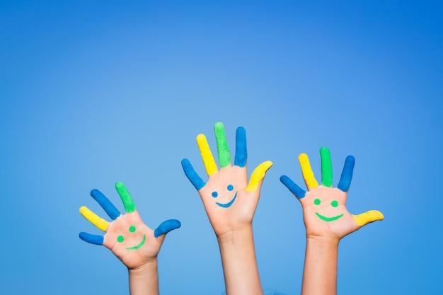 Crianças felizes com um smiley nas mãos contra o fundo do céu azul de verão