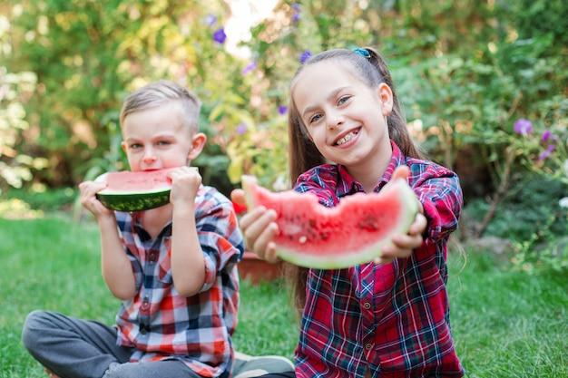 Crianças felizes comendo melancia no jardim. as crianças comem frutas ao ar livre. lanche saudável para crianças. menina e menino brincando no jardim, mordendo uma fatia de melancia.