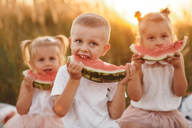 Crianças felizes comendo melancia no verão ao pôr do sol no campo. piquenique de verão. infância feliz. foco seletivo.