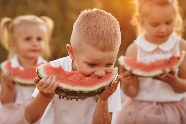 Crianças felizes comendo melancia no verão ao pôr do sol