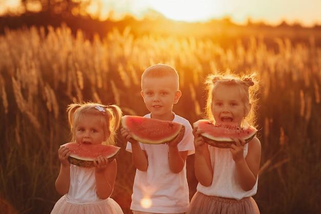 Crianças felizes comendo melancia