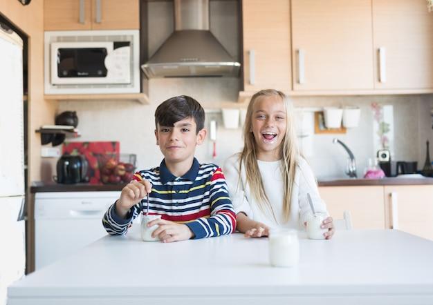 Crianças felizes comendo um iogurte.