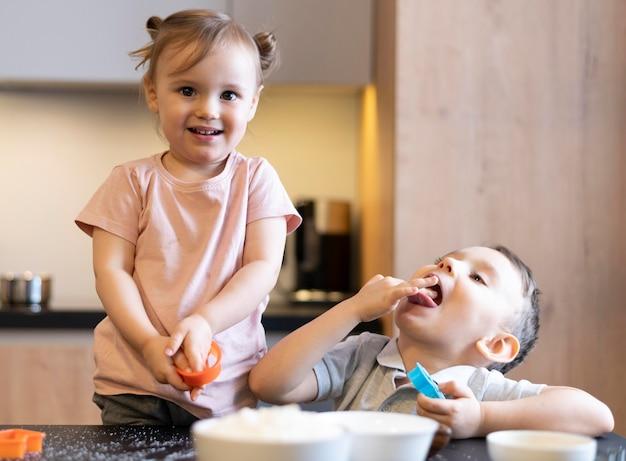 Crianças felizes cozinhando em tiro médio