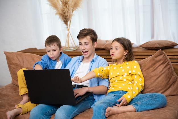 Crianças felizes, crianças se divertindo usando laptop juntas, sentadas no sofá, relaxando em casa