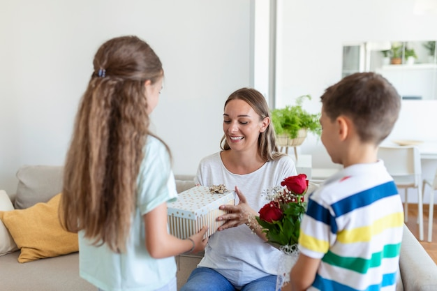 Crianças felizes, dando um presente de flores para a mãe. feliz dia das mães! crianças, menino e menina, parabenizam a mãe sorridente, dão a ela um buquê de flores e uma caixa de presente durante a celebração do feriado