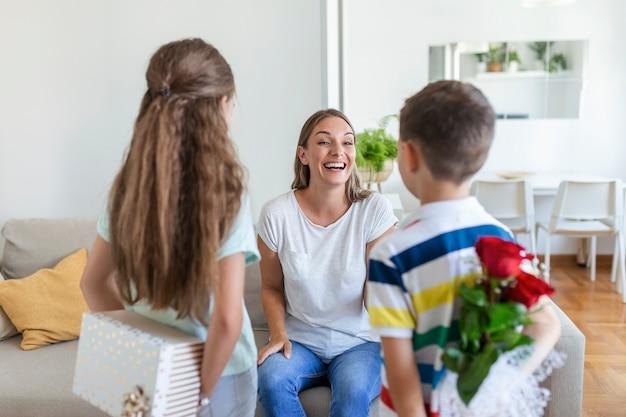 Crianças felizes, dando um presente de flores para a mãe. feliz dia das mães! crianças, menino e menina, parabenizam a mãe sorridente, dão um buquê de flores e uma caixa de presente durante a celebração do feriado