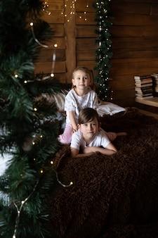 Crianças felizes de pijama brincando na manhã de natal perto do pijama da árvore de natal
