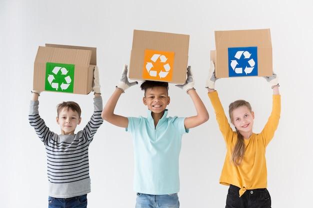 Crianças felizes de vista frontal segurando caixas de reciclagem