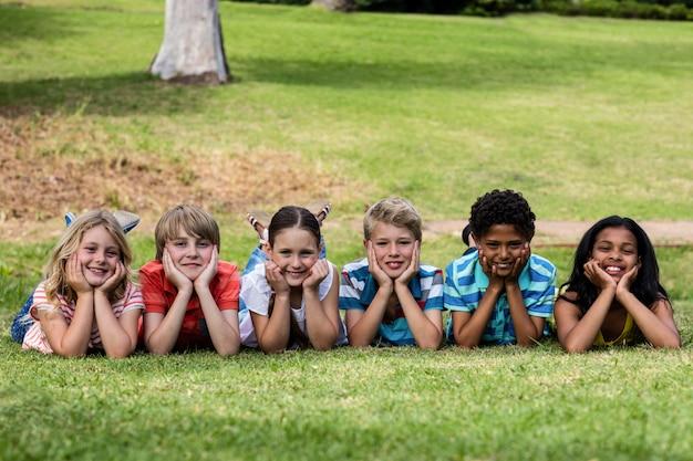 Crianças felizes, deitado na grama