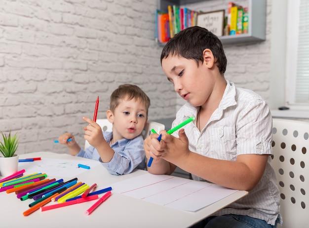 Crianças felizes desenham na sala de aula que a criança aprende em casa
