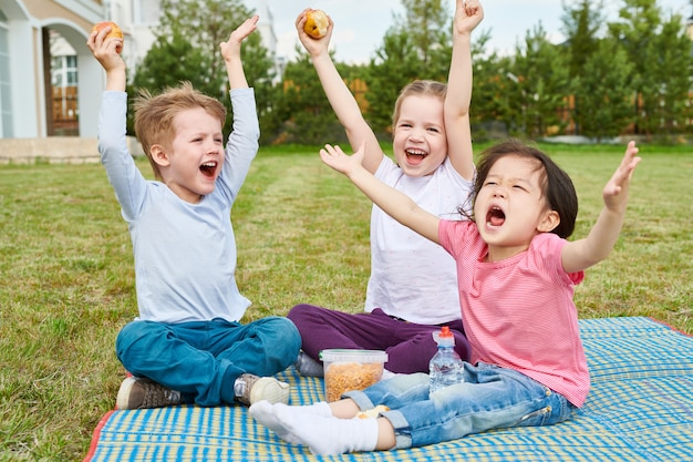 Crianças felizes, desfrutando de piquenique no gramado