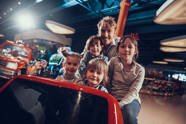Crianças felizes dirigindo o carro de brinquedo no centro