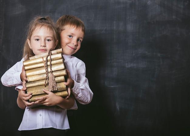 Crianças felizes do ensino fundamental na sala de aula com livros nas mãos