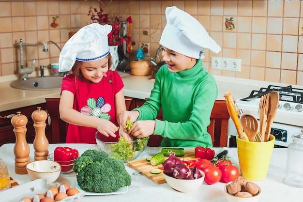 Crianças felizes e engraçadas da família estão preparando uma salada de legumes fresca na cozinha