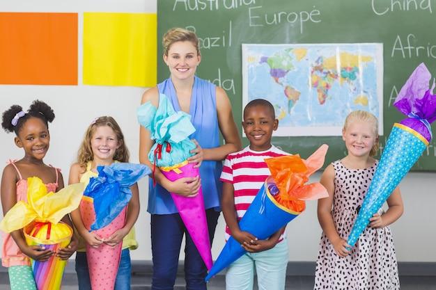 Crianças felizes e professor segurando presentes na sala de aula