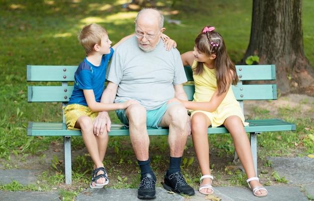 Crianças felizes e seu avô estão brincando juntos no banco do parque