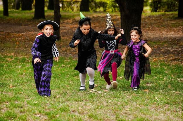 Crianças felizes em fantasias de halloween correndo no gramado