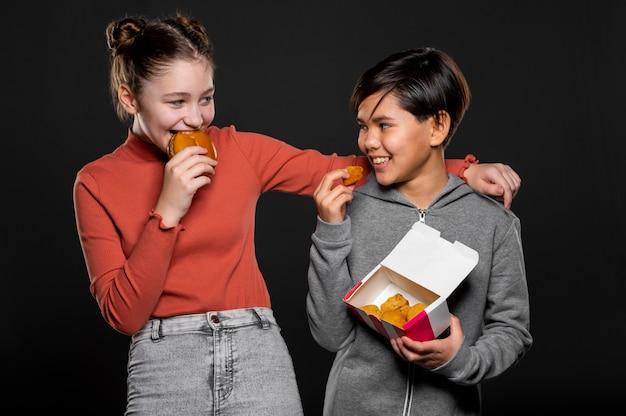 Crianças felizes em tiro médio com fast food