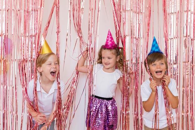 Crianças felizes em tiro médio usando chapéus de festa