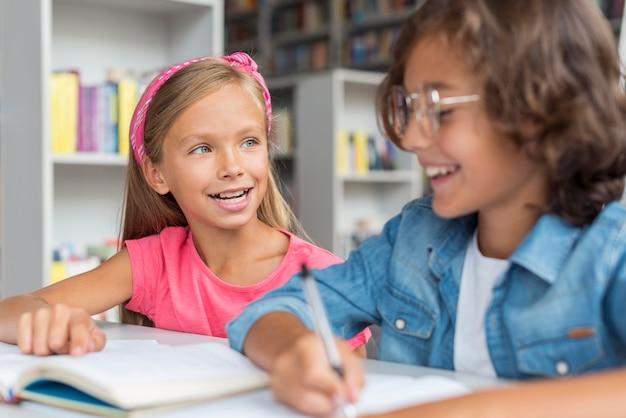 Crianças felizes enquanto fazem seus deveres de casa na biblioteca