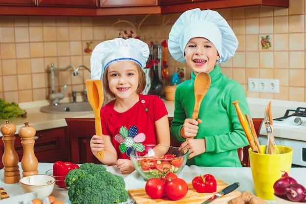 Crianças felizes estão preparando salada de legumes fresca na cozinha