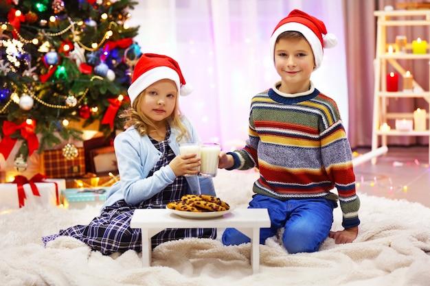 Crianças felizes fazendo uma refeição na sala decorada de natal