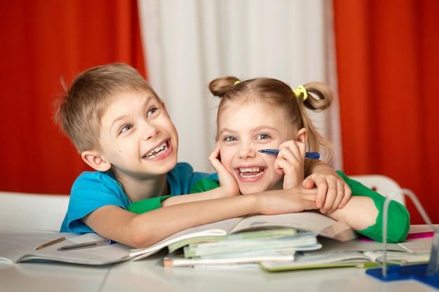 Crianças felizes, irmão e irmã, crianças em idade escolar fazendo lição de casa