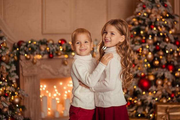 Crianças felizes irmão e irmã no fundo da lareira e árvore de natal em luzes