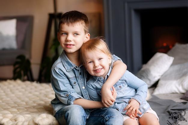 Crianças felizes, irmão e irmã, sentar e abraçar