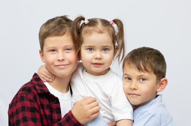 Crianças felizes isoladas em branco dois meninos e uma menina