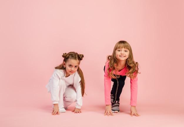Crianças felizes isoladas na parede do estúdio rosa coral