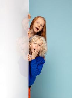 Crianças felizes isoladas no fundo azul do estúdio. parece feliz, alegre, sincero. copyspace. infância, educação, conceito de emoções