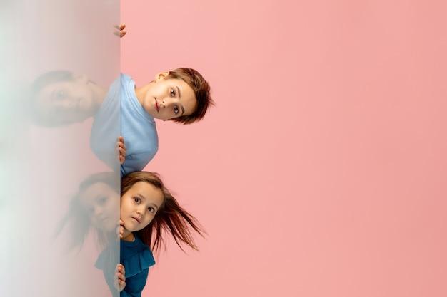 Crianças felizes isoladas no fundo do estúdio rosa coral. parece feliz, alegre, sincero. copyspace. infância, educação, conceito de emoções