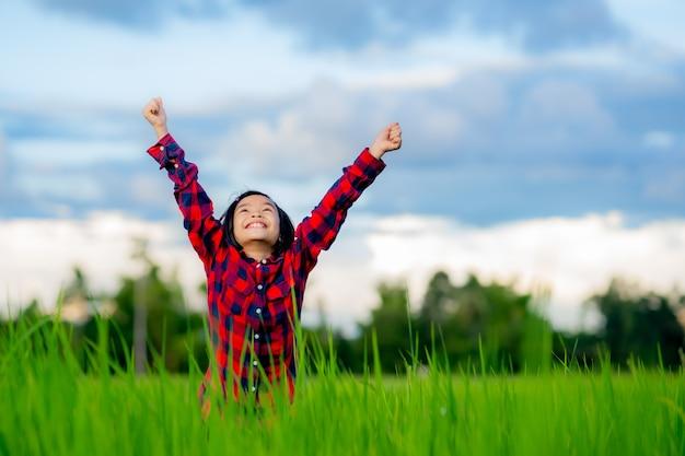 Crianças felizes levantam a mão e sorriem no campo de arroz de uma fazenda orgânica no fundo do céu azul