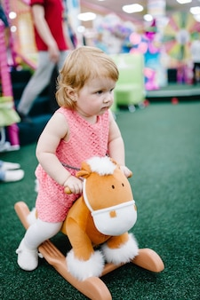 Crianças felizes, menina balançando em um cavalo de brinquedo é jogada na sala de jogos infantil em uma festa de aniversário.