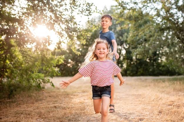 Crianças felizes menino e menina brincam no parque. o irmão mais velho brinca com sua irmã na natureza nos raios do sol de um dia de verão.