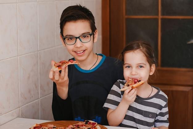 Crianças felizes, menino e menina, comendo pizza em casa